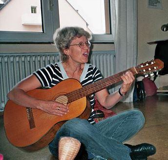 Kursleiterin spielt Gitarre und singt